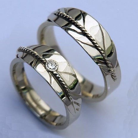 Native American wedding rings featuring silver eagle feathers and a diamond in the ladies' ring