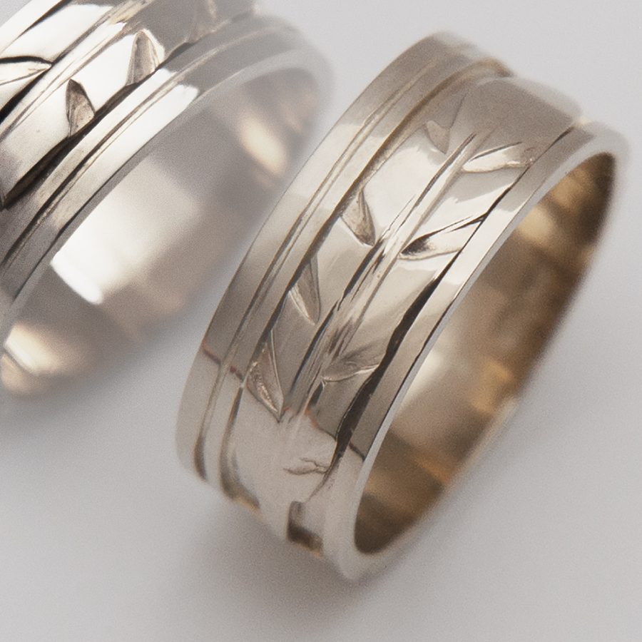 Oshki-waaseyaaban eagle feather wedding rings detail image