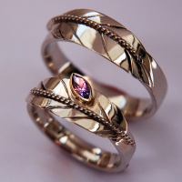 Native American-inspired eagle feather wedding rings set with an amethyst stone